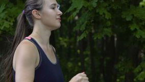 Side view of woman running in forest, outdoor female runner in fresh air jogging