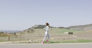 Side view of woman running among nature stock video footage