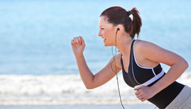 Side view of a woman running by the sea Royalty Free Stock Image