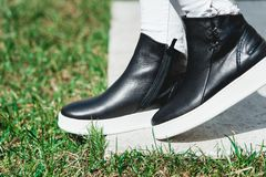 Side View Of Woman`s Black Leather Ankle Boots. Outdoor Shot Over White Stone in park stock photos