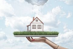 Side view of woman`s hand holding tablet with green grass and little detached house on screen, with rain cloud above. House. Digital tech is changing building stock illustration