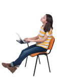 Side view of  woman sitting on a chair to study with a laptop. Stock Photo