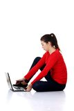Side view woman sitting cross-legged with laptop Stock Images