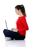 Side view woman sitting cross-legged with laptop Stock Photos