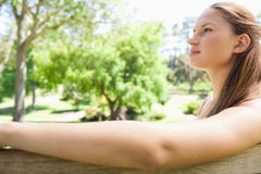 Side view of a woman sitting on a park bench Stock Photo