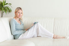 Side view of woman sitting on the sofa with a magazine Stock Photos