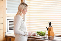 Side view of woman slicing ingredients for her salad Stock Image