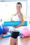 Side view of woman smiling while holding yoga mat Royalty Free Stock Images