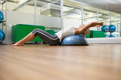 Side view of woman stretching her back in fitness studio Stock Photo