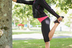 Side view of a woman stretching her leg during exercise at park Royalty Free Stock Photography