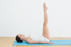 Side view of a woman stretching legs on exercise mat stock photo