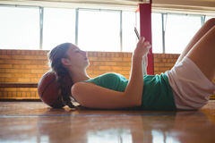 Side view of woman using digital tablet in court. Side view of woman using digital tablet while lying on floor in basketball court Stock Images