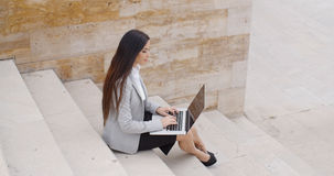 Side view of woman using laptop on stairs Royalty Free Stock Photo