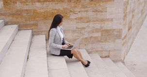 Side view of woman using laptop on stairs Royalty Free Stock Photos