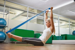 Side view of woman using resistance band in fitness studio Stock Photo