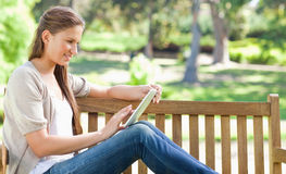 Side view of a woman using a tablet computer on a park bench Royalty Free Stock Photos