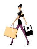 Side view of woman walking. There is a girl carrying few shopping bags. She looks so fancy and sexy Royalty Free Stock Images