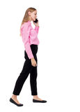 Side view of a woman walking with a mobile phone. back view ofgi Stock Images