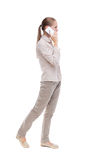 Side view of a woman walking with a mobile phone. back view ofgi Stock Image