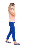 Side view of a woman walking with a mobile phone. back view ofgi Royalty Free Stock Images
