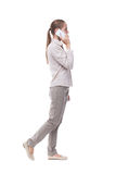 Side view of a woman walking with a mobile phone. back view ofgi Royalty Free Stock Photography