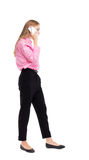 Side view of a woman walking with a mobile phone. back view Royalty Free Stock Photography