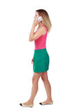 Side view of a woman walking with a mobile phone. Royalty Free Stock Photography