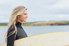 Side view of woman in wet suit holding surfboard at beach Royalty Free Stock Images