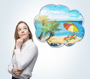 A side view of a woman who dreams about summer vacation on the beach. A nice summer place is drawn in the thought bubble. Concrete. Wall Royalty Free Stock Image