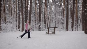Side view of a woman who is energetically in the winter park. Around her, pines and other spruce trees. She walks past stock footage