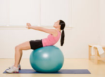 Side view of woman working out on exercise ball. In fitness studio Stock Photos
