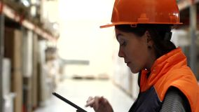 Woman in warehouse typing on tablet. Side view of woman in workwear looking up on shelves and typing on digital tablet in warehouse stock video footage