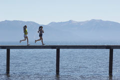 Side View Of Women Running Along Pier Royalty Free Stock Images