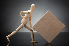 Wooden Dummy Lifting Cardboard Box Suffering From Back Pain. Side View Of A Wooden Dummy Lifting Cardboard Box Suffering From Back Pain stock images