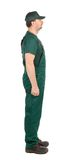 Side view. Worker in green overalls. Stock Image