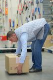 Side view worker while lifting box in warehouse Stock Images