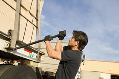 Side View Of A Worker Tightening Belt Of A Trailer With Metal Rod. Side view of a middle aged male warehouse worker tightening belt of a trailer with metal rod Stock Photo
