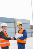 Side view of workers shaking hands in shipping yard Stock Images