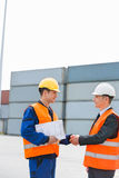 Side view of workers shaking hands in shipping yard Royalty Free Stock Photo