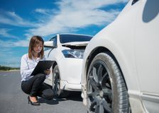 Side view of writing on clipboard while insurance agent examining car after accident stock images