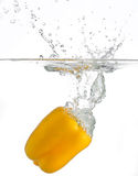 Yellow pepper splashing in water. Side view of yellow bell pepper splashing in water, white background Royalty Free Stock Photo