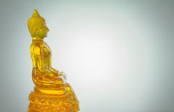 Side view of yellow  glass buddha statue on white bac Royalty Free Stock Photography