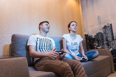 Side view of young addicted couple playing video games Royalty Free Stock Photos