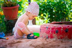 Girl playing with sand in garden. Side view of young adorable toddler girl sitting and playing with plastic toys at sandbox in the garden stock images