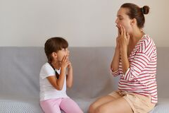 Side view of young adult Caucasian language therapist teaching little kid sounds pronunciation, working on speech defects or