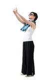 Side view of young adult woman taking photo with mobile phone holding with both hands Royalty Free Stock Photo