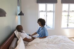Female doctor consoling senior man in bedroom. Side view of young African American female doctor consoling senior African American men in bedroom at home royalty free stock images