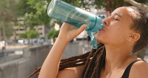 Side view of young African American woman drinking water in the city 4k stock video