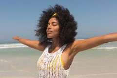 Young African American woman with eyes closed and arms stretched out standing on the beach. Side view of young African American woman with eyes closed and arms stock photos