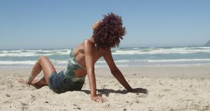 Side view of young African american woman relaxing on the beach 4k stock video footage